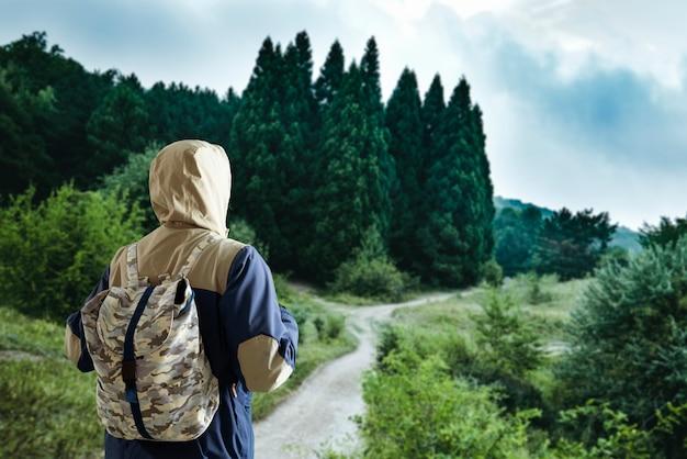 Eine person mit rucksack wandert und klettert auf dem gipfel des berges