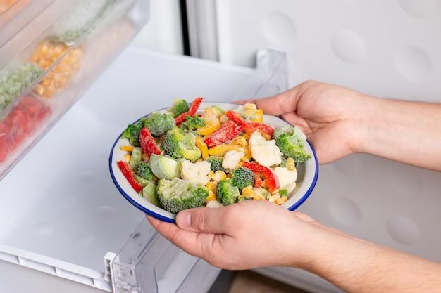 Eine person nimmt einen teller mit gefrorenem gemüse aus dem gefrierschrank des kühlschranks. konzept von tiefkühlkost, langzeitlagerungsprodukten.