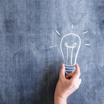 Eine person, welche die glühlampe gezeichnet auf tafel hält