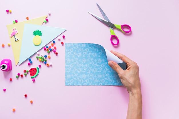 Eine personenhand, die blaues papier des faltens über dem rosa hintergrund hält