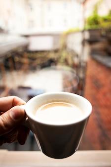 Eine personenhand, die den tasse kaffee nachdenkt über fensterglas hält