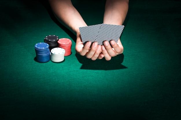 Eine personenhand, die spielkarte mit dem stapeln von pokerchips auf kasinotabelle hält