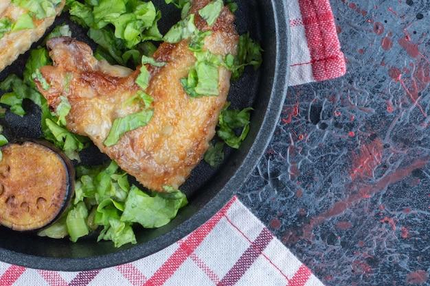 Eine pfanne mit salat und gebackenem hühnerfleisch.
