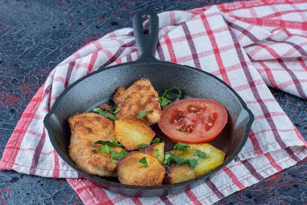 Eine pfanne mit salat und gebackenem hühnerfleisch