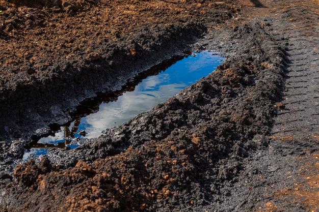 Eine pfütze aus verschüttetem rohöl in der furche vom lastwagen. umweltkatastrophe, umweltverschmutzung, umweltschäden