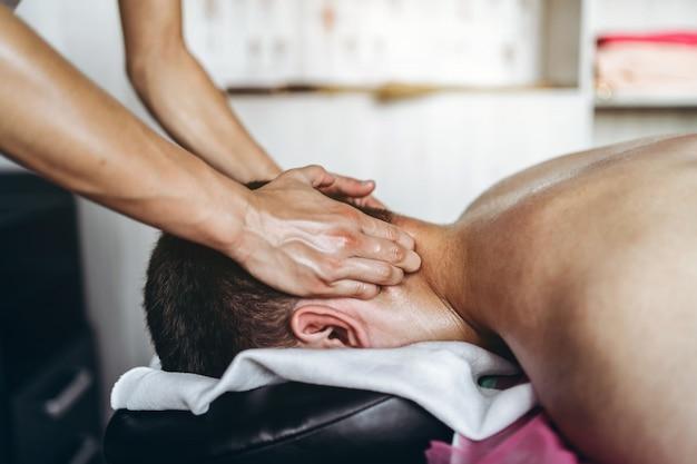 Eine physiotherapeutin, die eine nackenmassage für einen mann in der arztpraxis durchführt. nahaufnahme der hände, die massage tun
