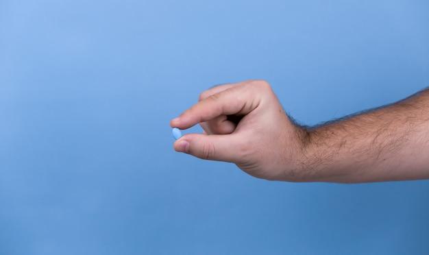 Eine pille in einer männlichen hand. ein mann hält pillen in der hand.