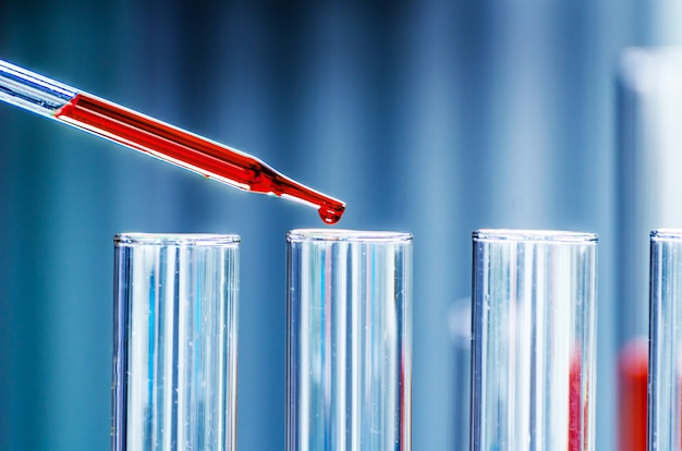 Eine pipettenfallprobe in ein reagenzglas, hintergrund der abstrakten wissenschaft
