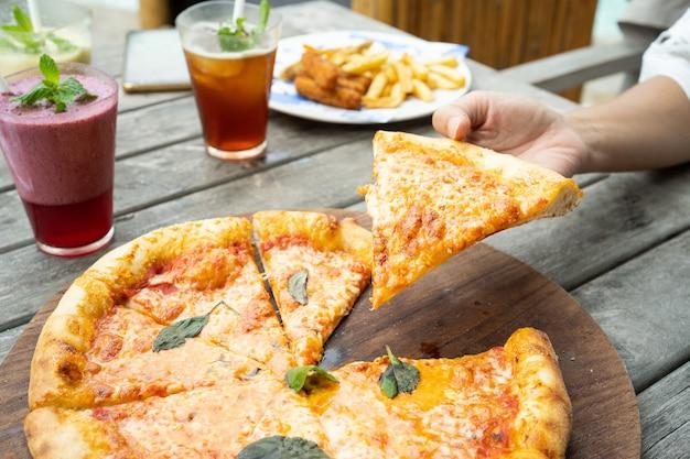 Eine pizza auf dem tisch nahm ein stück mit den händen und frischem saft