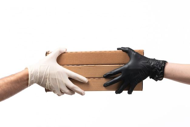 Eine pizzaschachtel mit vorderansicht wird von frau zu mann geliefert, beide in handschuhen auf weiß