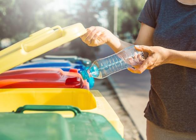 Eine plastikflasche wird in einem mülleimer entsorgt