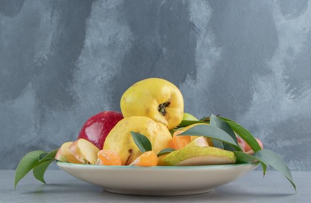 Eine platte mit einem stapel verschiedener früchte auf marmor