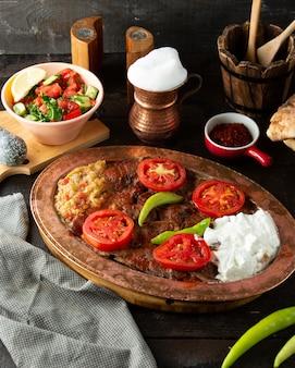 Eine platte mit iskender-kebab, serviert mit auberginensalat und joghurt