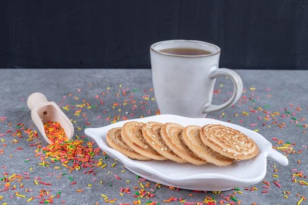 Eine platte mit keksen, eine kugel mit süßigkeiten und eine tasse tee
