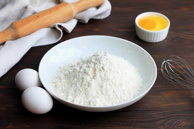 Eine platte mit mehl, eiern, einem nudelholz und wischen auf einem weißen hölzernen hintergrund.