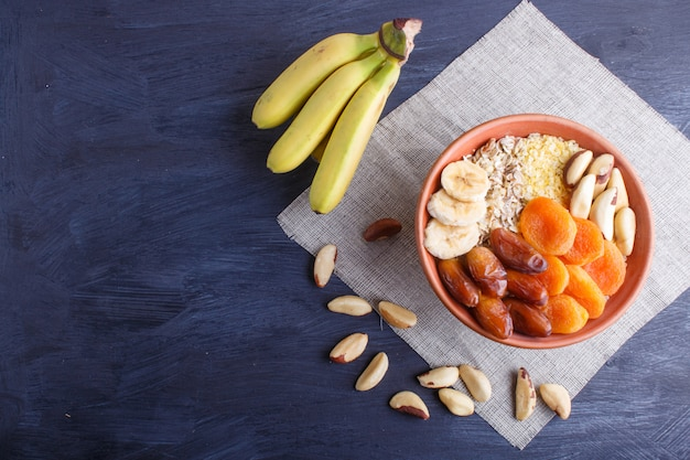 Eine platte mit müsli, banane, getrocknete aprikosen, datteln, paranüsse auf einem schwarzen hölzernen hintergrund.