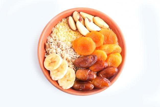 Eine platte mit müsli, banane, getrockneten aprikosen, datteln, paranüssen