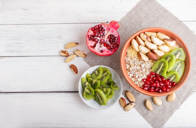 Eine platte mit müsli, kiwi, granatapfel, paranüsse auf einem weißen hölzernen hintergrund.