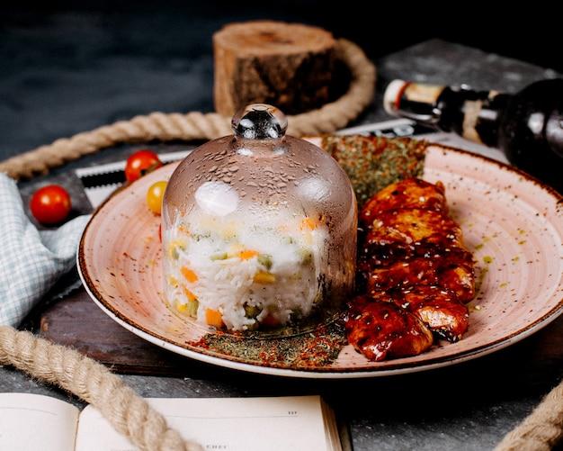 Eine platte reisgericht mit gemüse unter der glasabdeckung mit hühnchenstücken und kräutern
