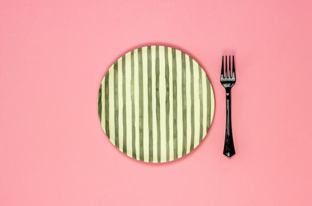 Eine platte und eine gabel auf einem rosa hintergrund. minimalismus.