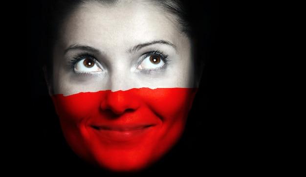 Eine polnische flagge auf einem weiblichen gesicht auf schwarzem hintergrund
