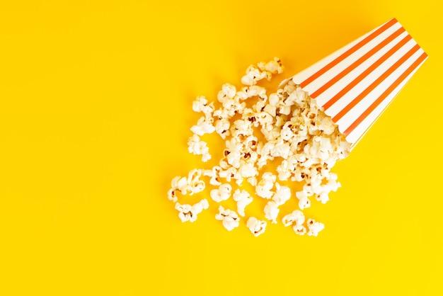 Eine popcorn-packung mit draufsicht gesalzen und lecker auf dem gelben hintergrund verteilt