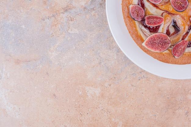 Eine portion kuchen mit lila feigen in einem weißen teller