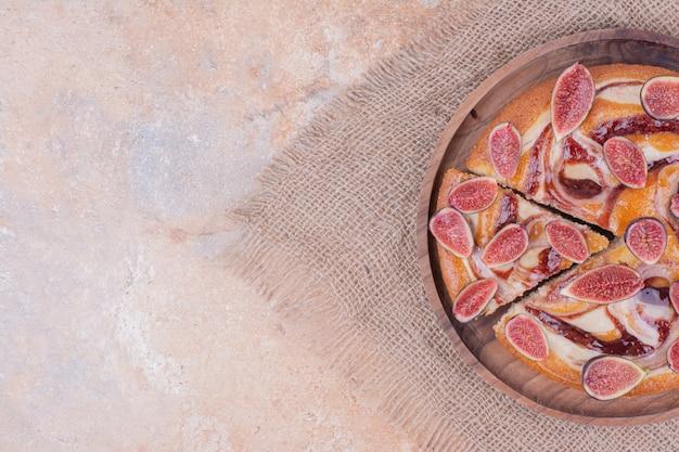 Eine portion kuchen mit lila feigen in einer holzplatte