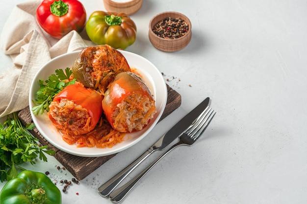 Eine portion paprika gefüllt mit fleisch und reis mit frischen kräutern auf hellem hintergrund. seitenansicht, platz zum kopieren.