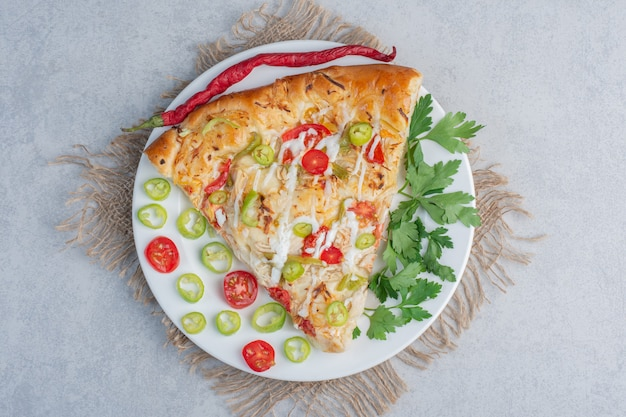 Eine portion pizza mit paprika und petersilienblättern auf marmoroberfläche
