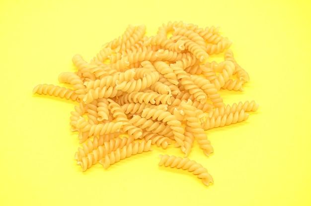 Eine portion rohe fusilli-nudeln an der gelben wand. klassische pastasorte, die sich aus vollkornsorten zu korkenzieher- oder spiralformen formte.