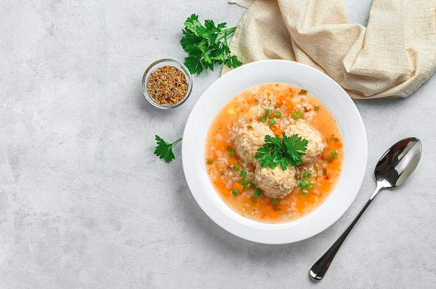 Eine portion suppe mit fleischbällchen, reis und gemüse auf hellgrauem hintergrund. ansicht von oben, kopienraum.