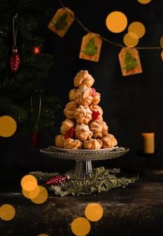 Eine postkarte für das neue jahr, profiteroles-kuchen werden auf einem hügel vor dem hintergrund eines weihnachtsbaums und eines bokehs gestapelt. foto in hoher qualität