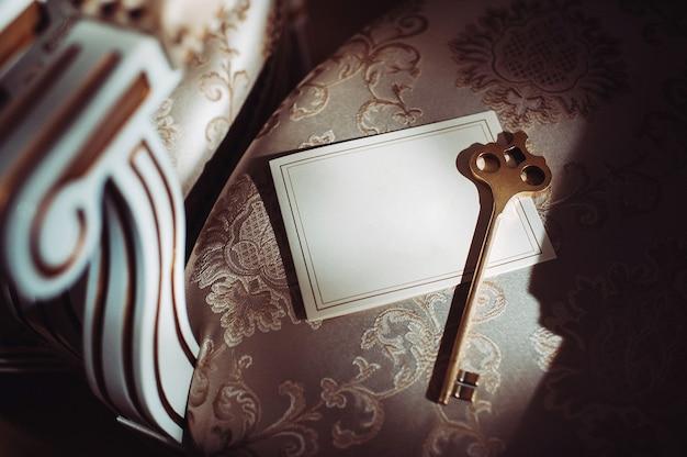 Eine postkarte und ein alter schlüssel auf dem hintergrund eines alten natürlichen stuhls.