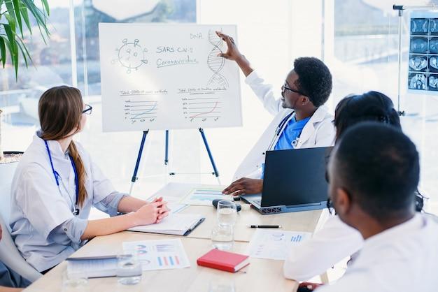 Eine professionelle gruppe von multiethnischen ärzten oder praktikanten mit mentor trifft sich und macht sich im krankenzimmer notizen. gesundheitskonzept.