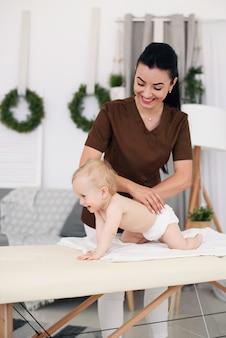 Eine professionelle masseurin massiert ein kleines baby. kindermassage auf der couch in einem modernen gemütlichen raum.