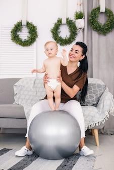 Eine professionelle masseurin mit glücklichem baby, das übungen mit fitnessball am medizinischen raum tut. gesundheitswesen und medizinisches konzept.