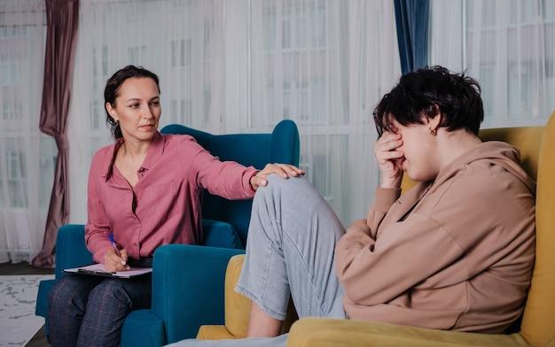 Eine psychologin sitzt auf einem stuhl und berät ein junges mädchen in einem raum