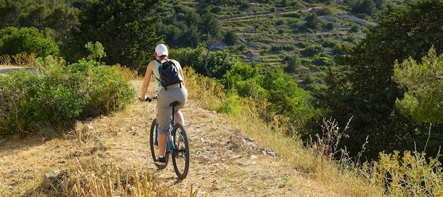 Eine radfahrerin fährt an einem sonnigen sommertag mit ihrem mountainbike einen bergpfad entlang