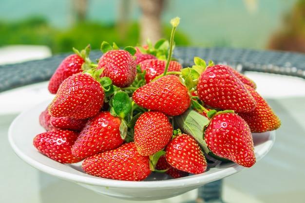 Eine reife erdbeere auf einem teller auf einem tisch.
