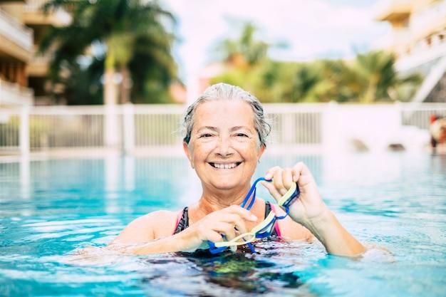 Eine reife frau, die alleine im pool schwimmt und trainiert - mit blick auf die kameraanzeige lächelnd