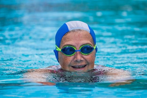 Eine reife frau, die am pool im wasser schwimmt - aktiver senior, der sport macht und einen fitness- und gesunden lebensstil hat