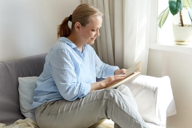 Eine reife frau in einem blauen hemd liest ein buch, während sie auf dem sofa am fenster sitzt.
