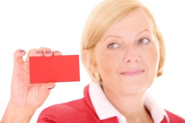 Eine reife frau mit einer roten visitenkarte auf weißem hintergrund