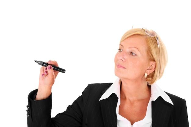 Eine reife hübsche geschäftsfrau, die auf einer transparenten tafel auf weißem hintergrund schreibt