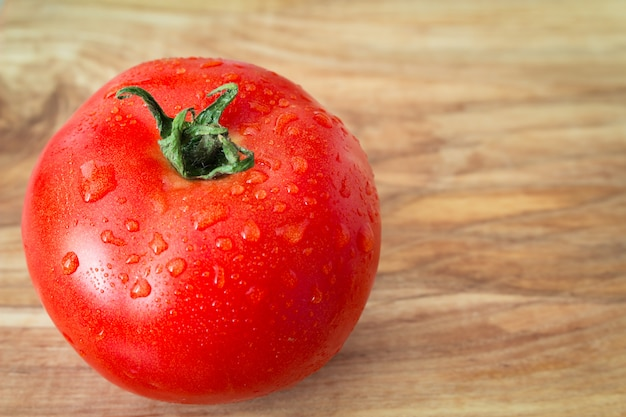 Eine reife tomate mit wasser fällt auf den hölzernen hintergrund