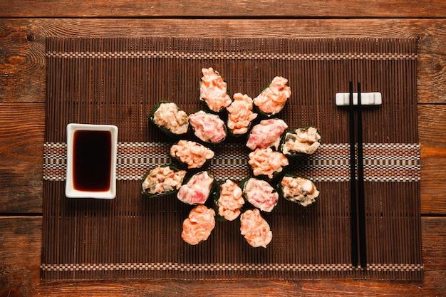 Eine reihe appetitlicher frischer gunkan-sushi-rollen, serviert auf brauner strohmatte, flach. japanische nationale meeresfrüchte, restaurantmenüfoto, essenskunst.