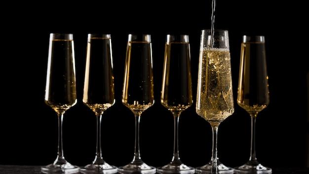 Eine reihe champagnergläser füllen. ein beliebtes alkoholisches getränk.