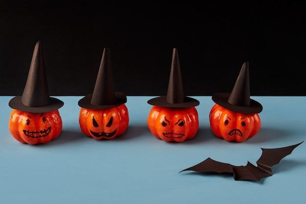 Eine reihe dekorativer kürbisse in schwarzen hüten, eine fledermaus auf einem blau-schwarzen hintergrund. halloween-feiertagskonzept.