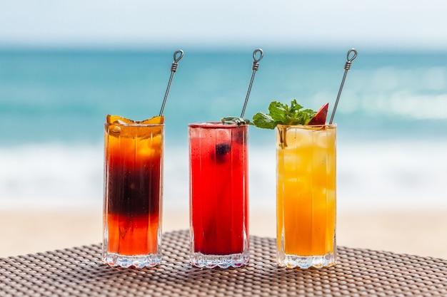 Eine reihe erfrischender fruchtcocktails, die auf dem tisch am strand in der nähe des türkisfarbenen meeres stehen?